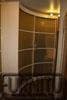 радиусный шкаф кремового цвета с золотым наполнением дверей шкафа