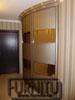 Светло-коричневый радиусный шкаф купе, с медными вставками в дверях.